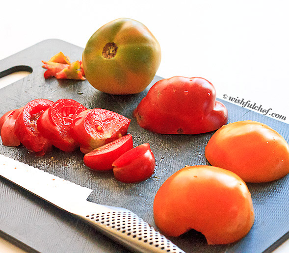 Core and slice tomatoes in half, then cut into wedges.